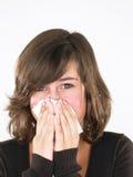Nez de soufflement de jeune femme Photographie stock