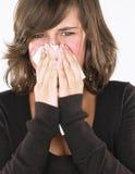 Nez de soufflement de jeune femme Photo stock