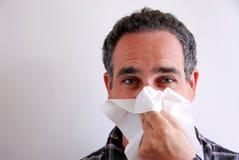 Nez de soufflement malade d'homme Images stock