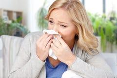 Nez de soufflement malade de femme au tissu ? la maison photo libre de droits