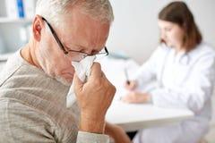 Nez et docteur de soufflement d'homme supérieur à l'hôpital photos stock