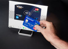 Nfc - contactless payment. Near field communication / contactless payment with mastercard credit card Stock Photography