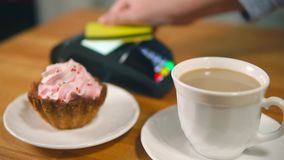 NFC contactless payment with credit card in cafe. Close-up shot of a customer paying for order in cafe using NFC technology on credit card. Focus on the cake and stock video footage