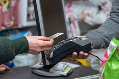 NFC technology, customer do payment with contactless credit card. Credit card reader implements payment execution. In the shop royalty free stock photos