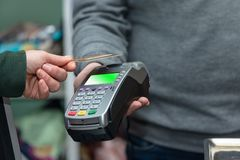 NFC technology, customer do payment with contactless credit card. Credit card reader implements payment execution. In the shop royalty free stock image