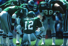 NFL Football Huddle. Professional Football players with the quarterback in the huddle with his teammates giving the next play Stock Images