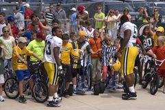 NFL Packers Football Tradition in Green Bay. Players from the Green Bay Packers partaking in the tradition of borrowing bikes from kids in order to ride to the stock photo
