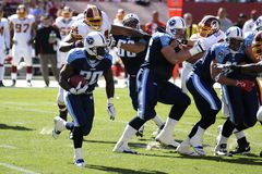 NFL Pro Football. NFL's Washington Redskins run defense pursues Tennessee Titans running back Royalty Free Stock Image