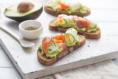 Fresh avocado toasts with red fish salmon and cucumber . Healthy vegetarian breakfast with rye wholegrain sandwiches royalty free stock photos