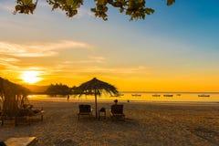 NGAPALI,缅甸- 2016年12月5日:在海滩的日落,与伞的轻便折叠躺椅 复制文本的空间 库存照片