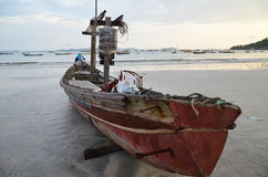 NGAPALI, MYANMAR- SEPTEMBER 27, 2016: Fisherman's boat fallen into ruin and disrepair on a beach. Traditional burmese fishing boat on the beach Royalty Free Stock Photos
