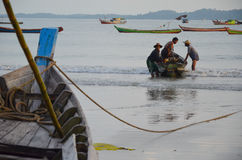 NGAPALI, MYANMAR- SEPTEMBER 27, 2016: Fisherman's boat fallen into ruin and disrepair on a beach. Traditional burmese fishing boat on the beach Royalty Free Stock Photo