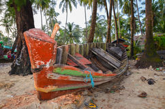 NGAPALI, MYANMAR- SEPTEMBER 27, 2016: Fisherman's boat fallen into ruin and disrepair on a beach. Traditional burmese fishing boat on the beach Stock Image