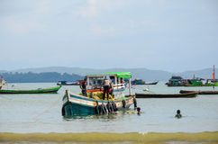 NGAPALI, MYANMAR- SEPTEMBER 25, 2016: Traditional old fishing boat bringing fish from the sea Royalty Free Stock Image