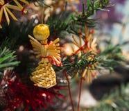 Ángel de la paja del juguete en la rama de árbol de navidad Imágenes de archivo libres de regalías