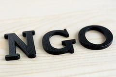 NGO-brieven op houten achtergrond Stock Afbeeldingen