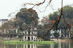 Ngoc Son Temple on Hoan Kiem Lake with trees in background and branches in foreground in Hanoi, Vietnam.  royalty free stock image