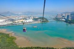 Ngong Ping Cable bil med turister över hamn, berg och stadsbakgrund, att besöka Tian Tan eller den stora Buddha som lokaliseras p arkivbild