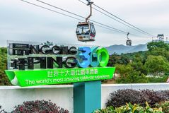 Ngong Ping 360 Skyrail on Lantau Island in Hong Kong is worlds most amazing cable car experience. Big sign on cable way line backg royalty free stock images