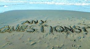 NÅGOT IFRÅGASÄTTER skriftligt på sanden av havet Arkivfoton