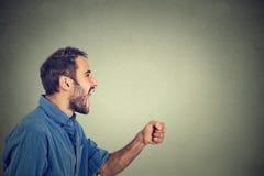 Ngry młody człowiek krzyczy z pięścią up w powietrzu Obraz Stock