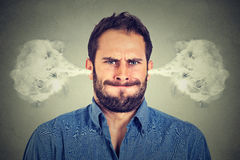Angry young man, blowing steam coming out of ears Stock Photo