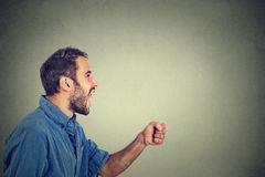 Ngry young man screaming with fist up in air Stock Image