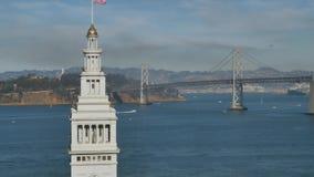 Ângulo alto que estabelece a balsa do tiro que constrói Clocktower e ponte da baía em San Francsico vídeos de arquivo