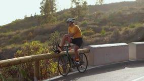 Ângulo largo que segue o tiro de uma bicicleta masculina da equitação do atleta do ajuste na estrada lisa longa no campo Ciclismo vídeos de arquivo