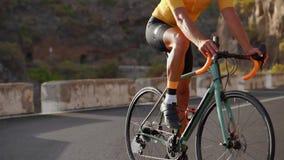 Ângulo largo que segue o tiro de uma bicicleta masculina da equitação do atleta do ajuste na estrada lisa longa no campo Ciclismo video estoque