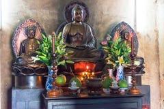 NHA TRANG, ВЬЕТНАМ - 13-ОЕ АПРЕЛЯ 2019: Статуя Будды с цветками и свечами в виске стоковое изображение rf