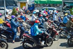 NHA TRANG, VIETNAM - APRIL 13, 2019: Plenty motorcyclists drive on road in rush hour on day royalty free stock photo