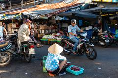 A woman sells dried fish at the street market stock photo