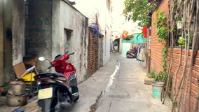 Video recording during motorbike ride on street of Nha Trang. Nha Trang, Vietnam - 18 February 2019: narrow city street with parked motorbikes and local flags on stock video footage