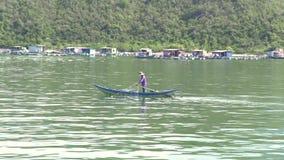 Nha Trang, Vietnam - octubre de 2018: pescador en la pesca del barco con la red de pesca en el mar azul en fondo verde de la mont almacen de metraje de vídeo