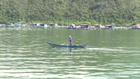 Nha Trang, Vietnam - Oktober 2018: Fischer auf Bootsfischen mit Fischernetz im blauen Meer auf grünem Gebirgshintergrund stock video footage