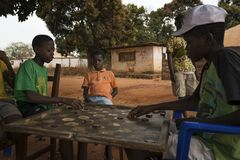 Group of children playing a game of checkers under a tree in the town of Nhacra in Guinea Bissau. Nhacra, Republic of Guinea-Bissau - January 28, 2018: Group of stock image
