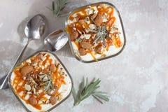Healthy breakfast. Greek yogurt, salted caramel, crumble, on stone white table royalty free stock photo