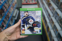 NHL 17 videogame on XBOX One. Bratislava, Slovakia, circa april 2017: Man holding NHL 17 videogame on Microsoft XBOX One console in store Stock Photo