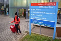 NHS Health Tourism. Photo of a Filipino woman with suitcase, backpack, passport and toothbrush at Rotherham NHS Hospital Stock Image