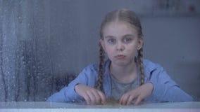 Niña aburrida que mira la cámara a través de ventana en el tiempo lluvioso, soledad metrajes