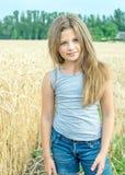 Niña adorable con el heredero largo que presenta en campo de trigo de oro en un día de verano Foto de archivo libre de regalías