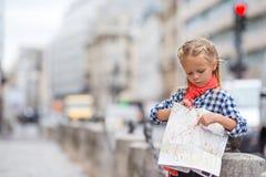Niña adorable con el mapa de la ciudad europea Foto de archivo libre de regalías