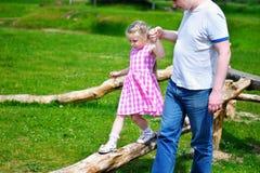 Niña adorable con el padre que lleva a cabo su mano que camina en la madera en día de verano soleado Fotos de archivo libres de regalías