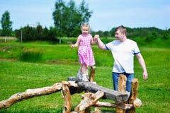 Niña adorable con el padre que lleva a cabo su mano que camina en la madera en día de verano soleado Fotografía de archivo