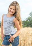 Niña adorable con el pelo largo que presenta en campo de trigo en un día de verano Fotografía de archivo libre de regalías