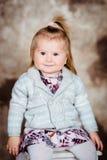 Niña adorable con el pelo rubio que se sienta en la silla blanca Foto de archivo