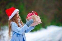 Niña adorable con el regalo de la caja de la Navidad en invierno al aire libre Fotografía de archivo