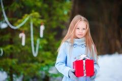 Niña adorable con el regalo de la caja de la Navidad en invierno al aire libre Fotos de archivo