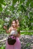 Niña adorable con la cesta de la paja adentro Foto de archivo